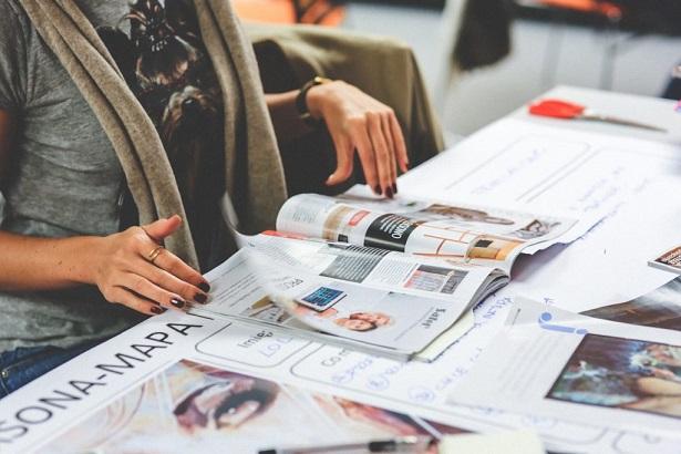 レディースデザイナーが雑誌を見て流行チェックをしている